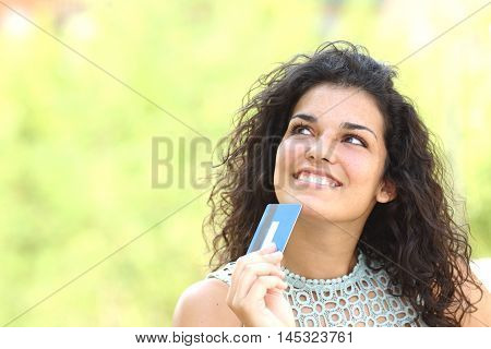 Shopper with a credit card thinking what to buy outdoors with a green background