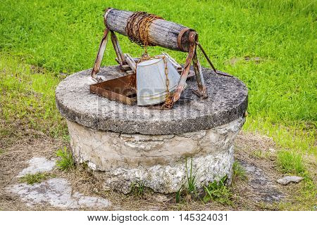 Old water well with bucket in summer day
