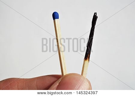 Male hand holding safety matches, one with with already burnt top and other unburnt fresh one as a symbol of contrast, choice or progression