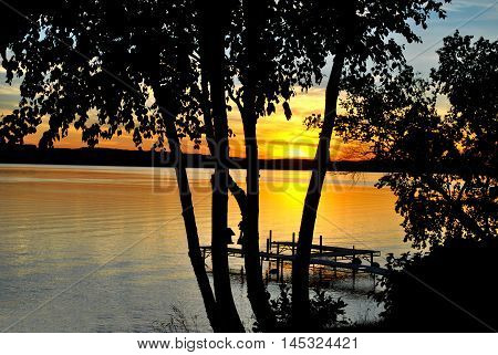 A Bright Summer Sunset Looking Through the Trees on a Large Lake