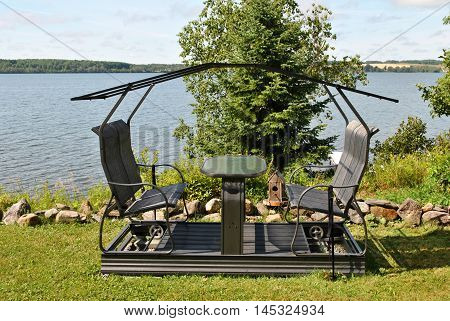 Metal Swinging Seat with a Lake in the Background