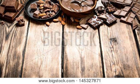 Chocolate cream with slices of chocolate and nuts. On a wooden table.