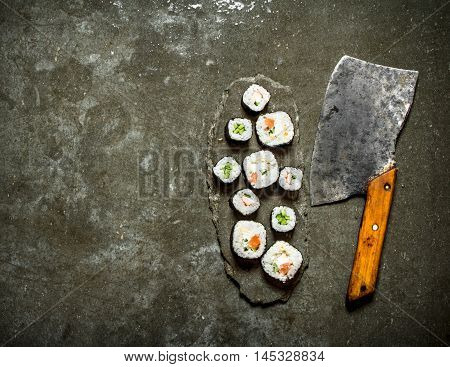 Japanese rolls with a hatchet for cutting. On the stone table.