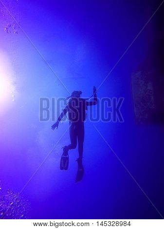 A backlit scuba diver silhouette. View of the scuba diver gear fins and bubbles underwater in the deep blue sea of Limassol Cyprus against the sunlight.