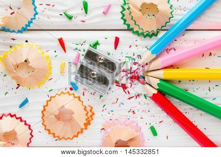 Colored Pencils And Pencil Sharpener On A White Wooden Background