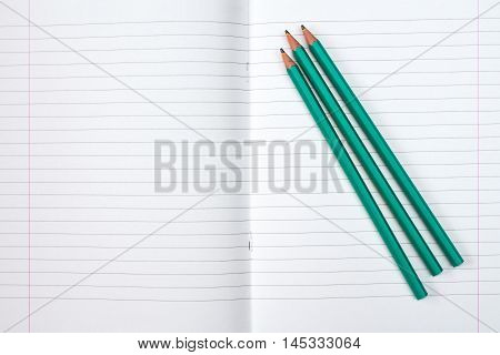 Lined exercise book and three pencils. Back to school concept.