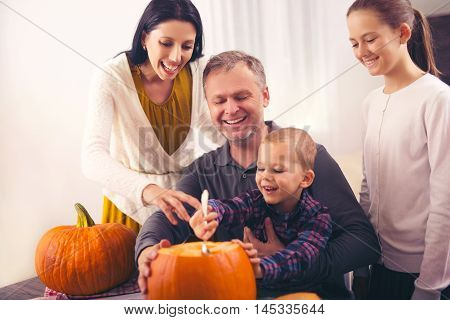 Family carving big orange pumpkin for Halloween