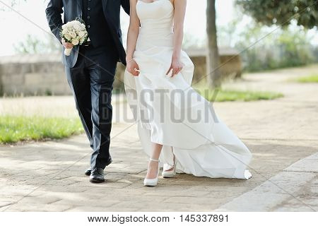Bride and groom walking together in a park in wedding day