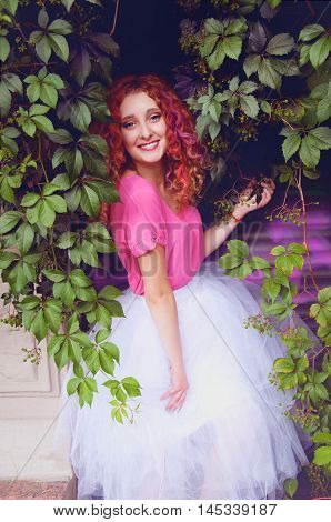 Happy smiling beautiful young woman with curly red hair with colorful hair pieces wearing bouffant skirt and magenta blouse standing among grape leaves