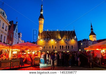 Old buildings restaurants and cafes of the Town Hall square in old historical area in the popular Baltic city Tallinn Estonia. Lights and illumination motion blurred people