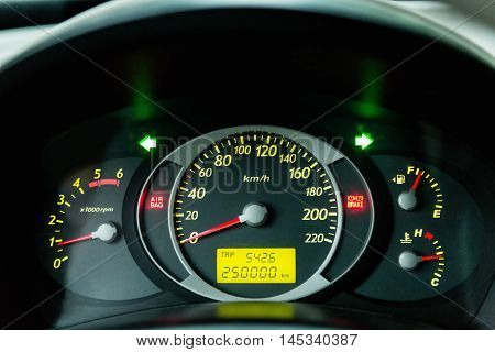 Car Dashboard. Close up image of illuminated car dashboard. 250 000 km without incident