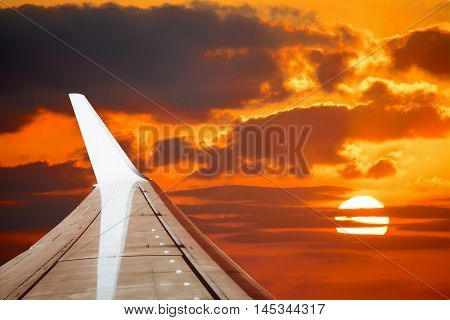 aiplane wing in an orange sky at sunset