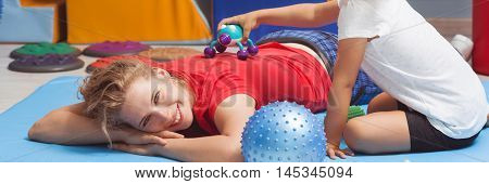 Girl touching her happy therapist with a massage device panorama poster