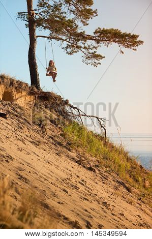Child swinging on seesaw above a sea