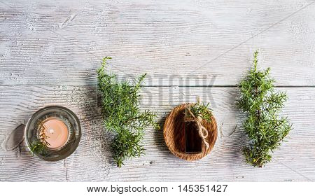 Juniper essential oil in a glass bottle on a wooden table. Used in medicine cosmetics and aromatherapy. Fresh green sprigs top view flat lay. Selective focus.