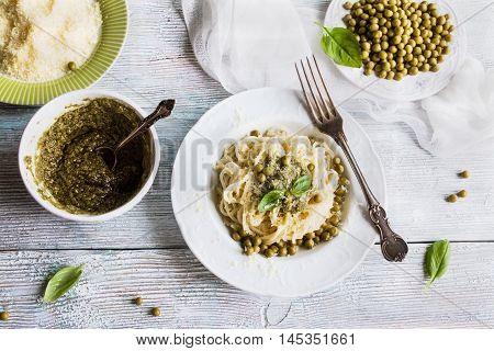 Pasta (spaghetti) green beans sauce pesto parmesan fresh basil. Vintage plates wooden table top view.