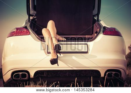 woman legs in high heel shoes from the trunk of car