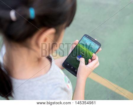 Chonburi, Thailand- September 2, 2016: Asian Little Girl Playing A Pokemon Go Game Outdoors. Pokemon