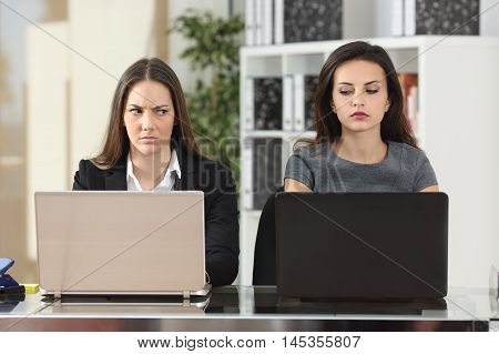 Front view of two angry businesswomen looking each other with hate working with laptops at office