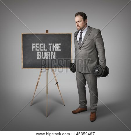 Feel the burn text on blackboard with businesssman holding weights