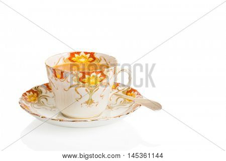 Cup of breakfast breakfast tea in antique teacup and saucer with spoon on a white background