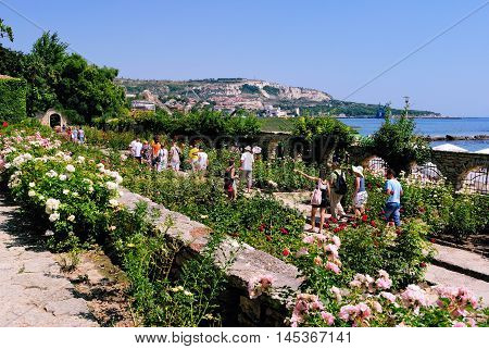 BALCHIK, BULGARIA - AUGUST 24, 2011: Tourists Passing through the Summer Rose Garden with Roses Abloom in the Botanical Garden on August 24, 2011 in Balchik, Bulgaria