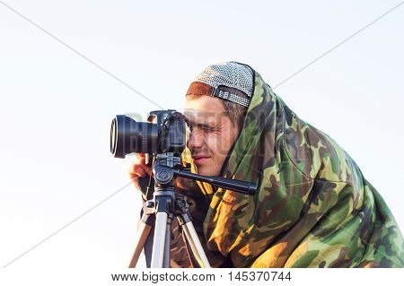 Closeup of a camouflaged paparazzi photographer taking picture with a camera on a tripod