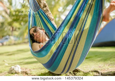 Woman taking a nap on a hammock in the beach poster