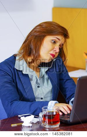 Young woman sick with flu, sitting by table using computer working, looking unwell and tired, medicines, tissues, glass of water on desk.