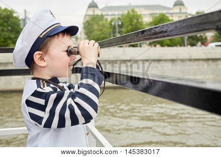Little boy dressed as a captain looks through binoculars standing at boat stern.