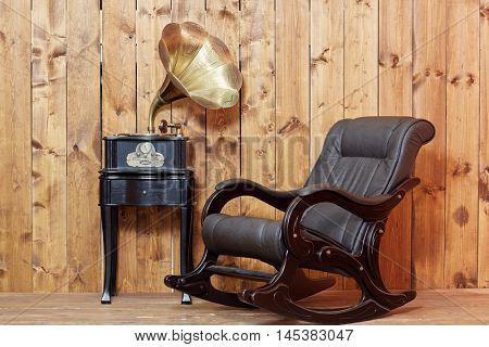 Empty rocking-chair in room next to the gramophone.