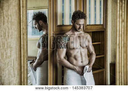 Sexy handsome young man standing shirtless in his bedroom against wooden wardrobe door