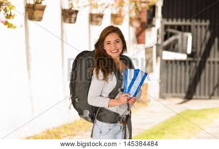 Young pretty woman wearing casual clothing and backpack standing in front of camera, smiling happily, holding travel tickets, backpacker concept.