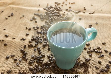 Cup Of Coffee With Skittered Beans On Sackcloth Background