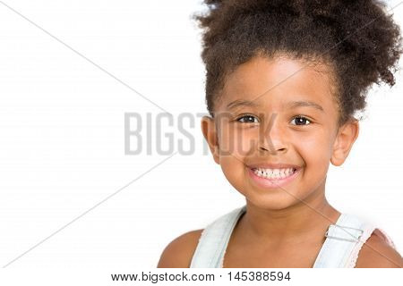 Cute preschool girl smiling in front of white background copy space
