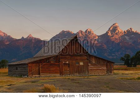 Mormon Row historical site in Jackson Grand Teton National Park Wyoming. Moulton Barn at first sunlight touches the Gran Teton peak with a beautiful old barn in summer