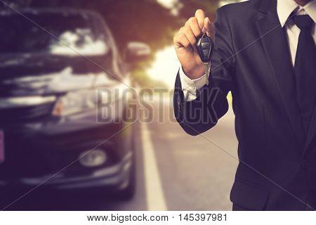 Businessman Showing A Car Key - Car Sale & Rental Business Concept.vintage Color