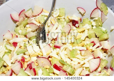 sliced cucumbers and radishes in a fresh vegetable salad