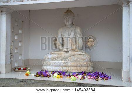 ANURADHAPURA, SRI LANKA - MARCH 12, 2015: Ancient marble sculpture of a seated Buddha at the foot of the Dagoba Ruvanvelisaya. Religious landmark