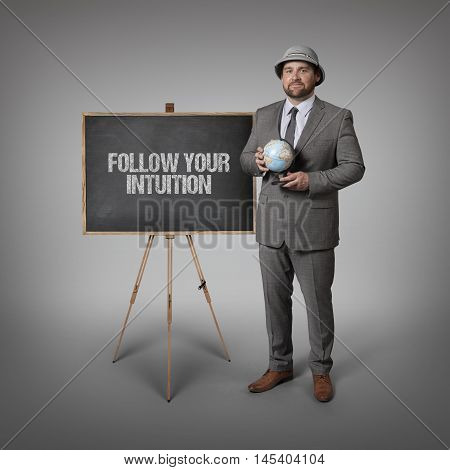 Follow your intuition text on blackboard with businessman holding globe in hands