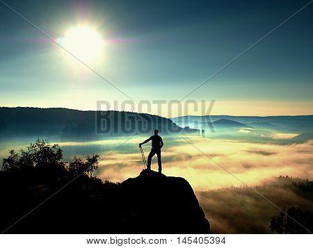 Tall Backpacker With Poles In Hand. Sunny Misty Daybreak In Rocks