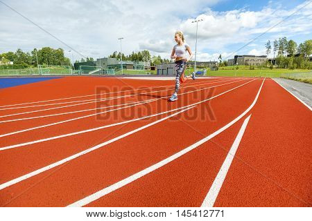Full length of fit young woman running on sports tracks