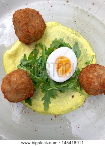 Fish / cheese fritters served on a hollandaise with a boiled egg and rocket