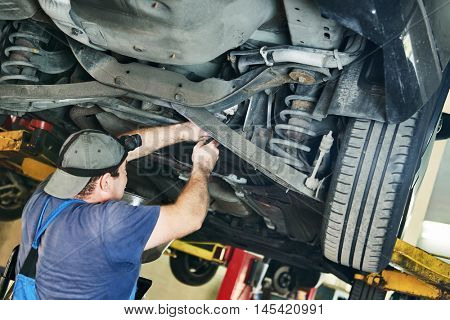 Automobile mechanic checks car suspension in service station