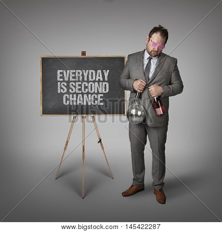 Everyday is second chance text on blackboard with businessman and key