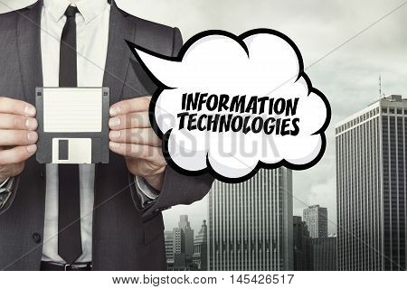 Information technologies text on speech bubble with businessman holding diskette