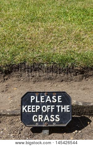 A polite sign warning people to Keep off of the Grass.