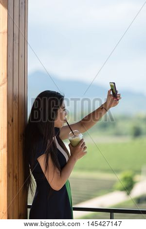 Beautiful asian women hold cup of ice mocha green tea coffee in open air coffee shop with mobile phone in hand and selfie