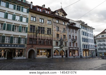 Lucerne Switzerland - May 03 2016: Colorful frescos decorate historic buildings on Weinmarkt. Despite the rainy weather the colors of the city show a variety of tourist attractions. These attractively decorated buildings are located almost in the center o