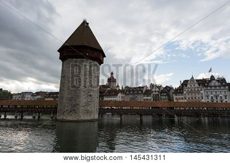 Lucerne Switzerland - May 03 2016: Evening view towards the Chapel Bridge (Kapellbruecke) together with the octagonal tall tower (Wasserturm) it is one of the Lucerne's most famous tourists attraction. Chapel Bridge joins two banks of the river Reuss. Bui